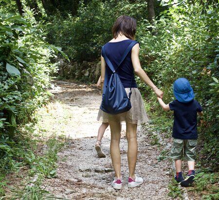 een gelukkige moeder loopt met haar kinderen door een bos