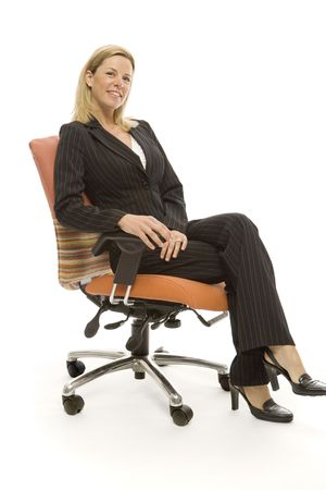 Businesswoman in a suit sits relaxing in a chair