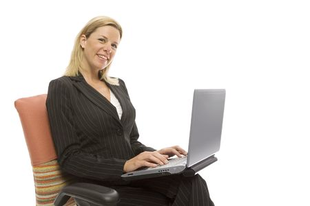 Businesswoman in a suit sits in a chair with a laptop