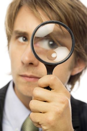 A businessman in a suit looks through a magnifying glass