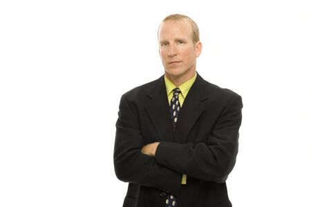 Businessman in a suit stands with arms crossed Stock Photo