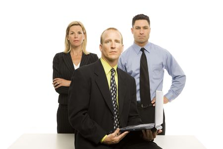 Three business people stand near a desk