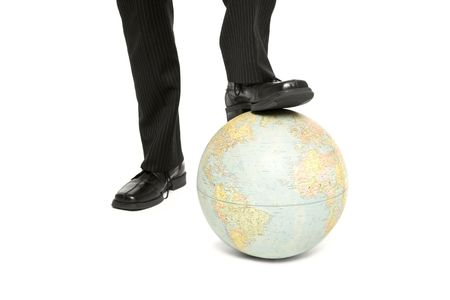 A businessman rests his foot on a blobe