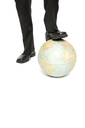 A business man rests is foot on a globe