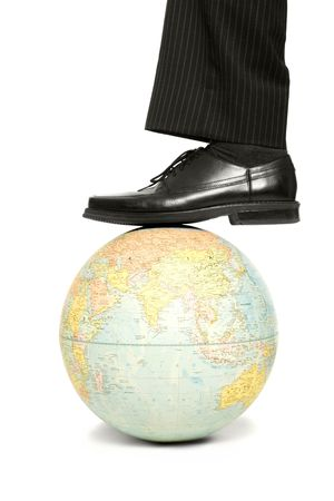 Businessman rests his foot on a globe Stock Photo