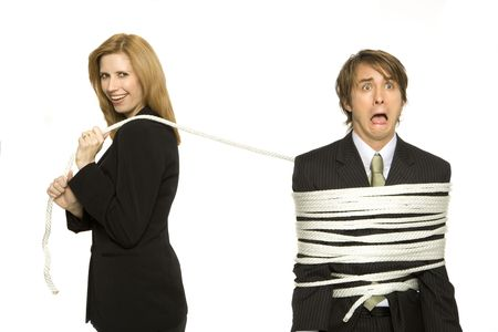 Businesswoman ties up a scared businessman Stock Photo
