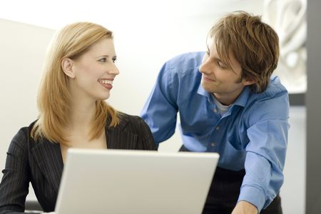 Workers happily share a white laptop computer Stock Photo
