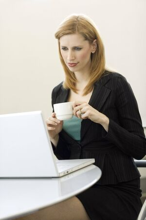 A businesswoman holds a cup of coffee as she uses a laptop