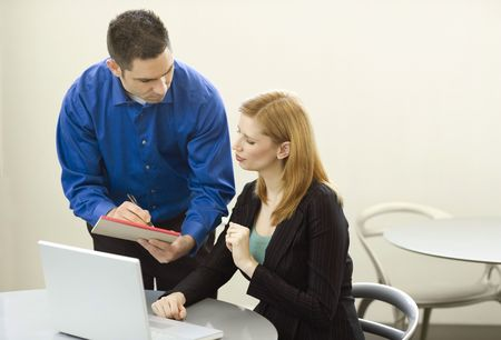 Two business people talk and use a laptop