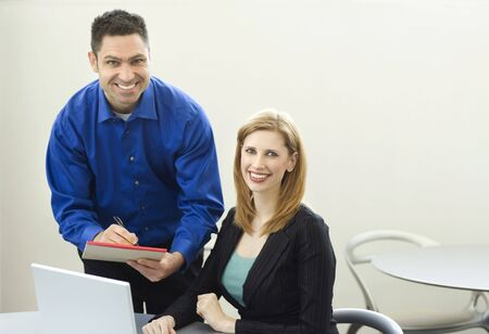 Two workers smile as they work near a desk