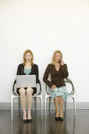 Two women sit in metal chairs and work photo