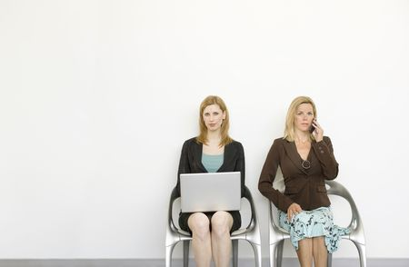 Two businesswomen sit in chairs and work