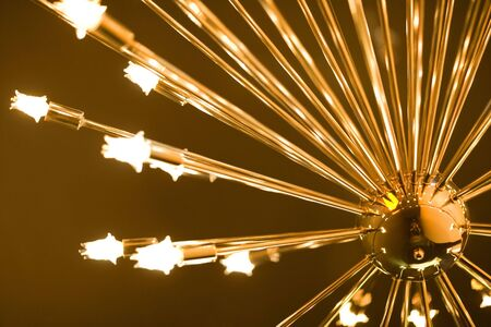 Golden chrome lamp with bulbs lights a room