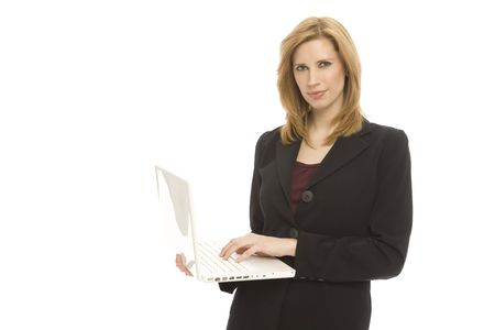 A businesswoman in a suit holds up a laptop