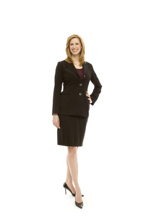 Businesswoman in a suit stands with confidence in a studio