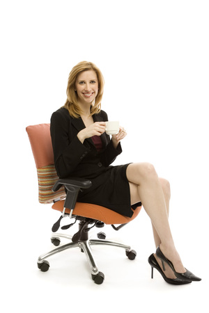 office furniture: Businesswoman relaxes in a chair with a cup of coffee