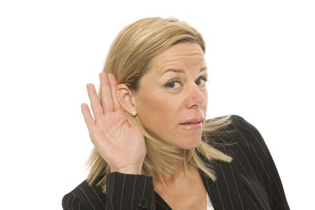 Businesswoman in a suit gestures with her hand to her ear to hear Stock Photo