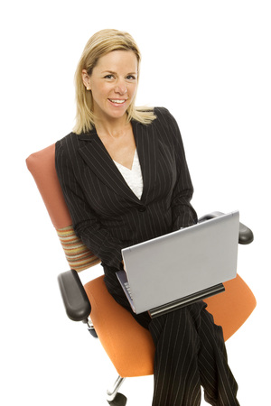 Businesswoman in a suit sits in a chair with a laptop smiling photo