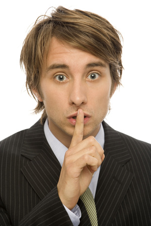 Businessman in suit gestures to be quiet with his finger