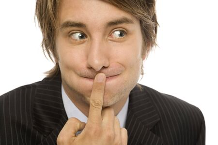 Businessman holds his finger to his lips to keep a secret