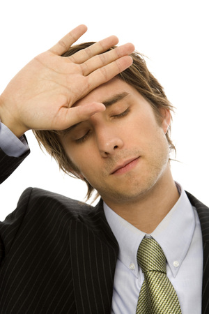 Businessman holds his hand to his head with exhaustion Stock Photo