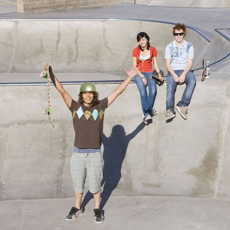 Skater raises his arms in triumph at a skate park with his friends