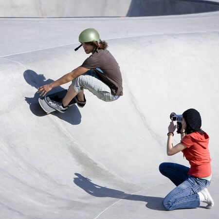 Skater does tricks as a friend films him with a camcorder