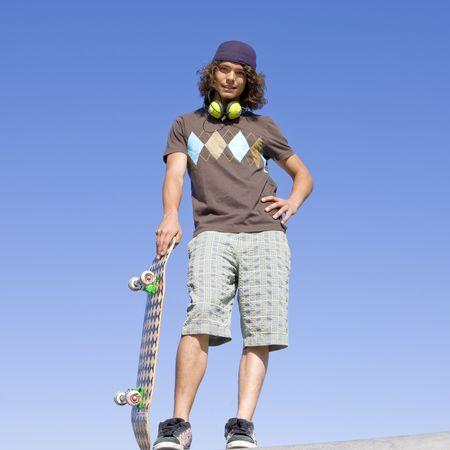 Skater with skateboard atop ramp Stock Photo