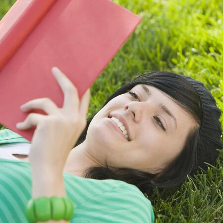 Teen studies in the grass with red book