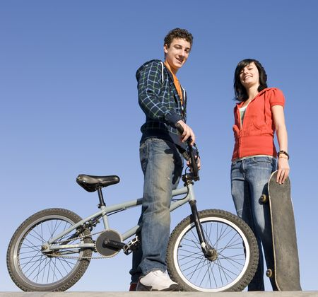 Teens with a bike and skateboard hang out at the skate park Stock Photo