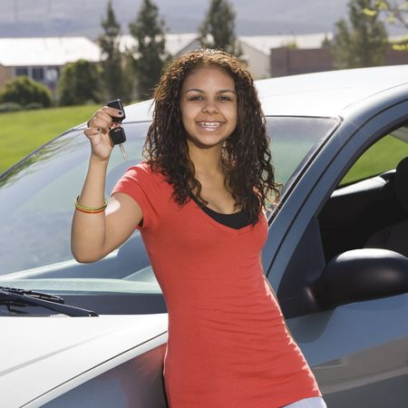 Happy teen holds up car keys and smiles