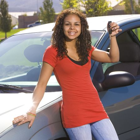 milestones: Happy teen holds up car keys and smiles