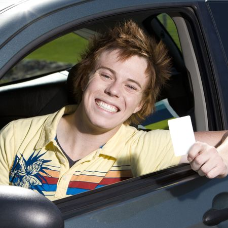 Happy teen with drivers licence smiles proudly