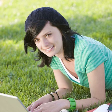 Teen studies with laptop in grass and smiles Stock Photo
