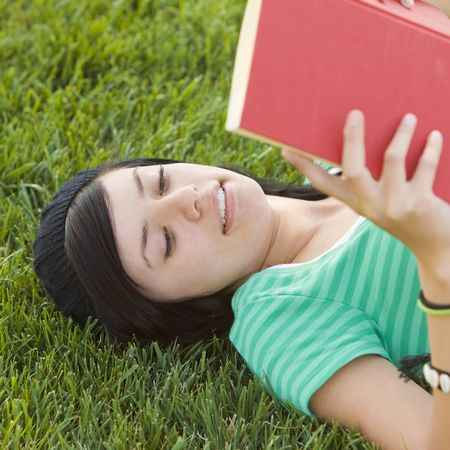 Happy teen studies with book in the grass Stock Photo - 3569630