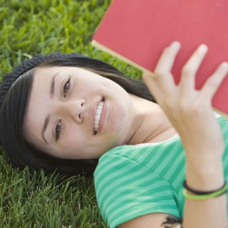 Happy teen studies with book in the grass Stock Photo - 3569520