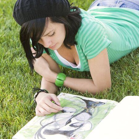 Teen draws in a sketch book while lying in grass Stock Photo