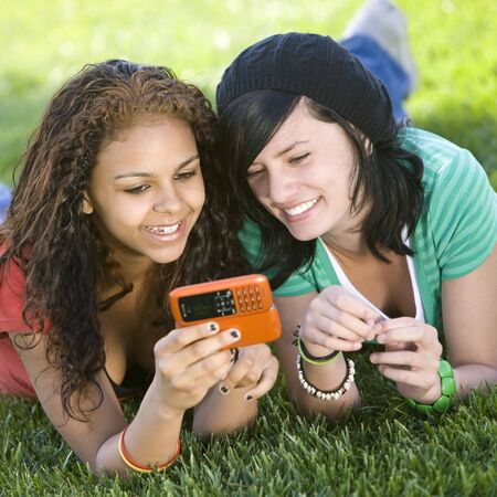 Girlfriends share a cell phone Stock Photo - 3569716