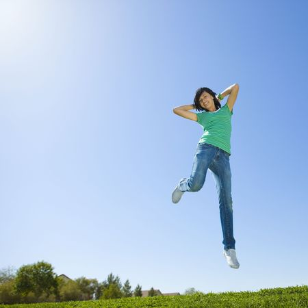 Happy teen jumps in air
