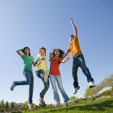 Four happy teens jump in the air