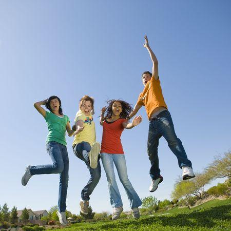 pareja de adolescentes: Cuatro adolescentes feliz salto en el aire Foto de archivo