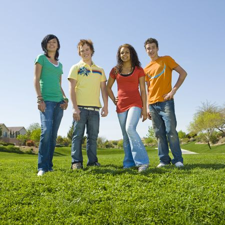 Group of teens stan in green grass