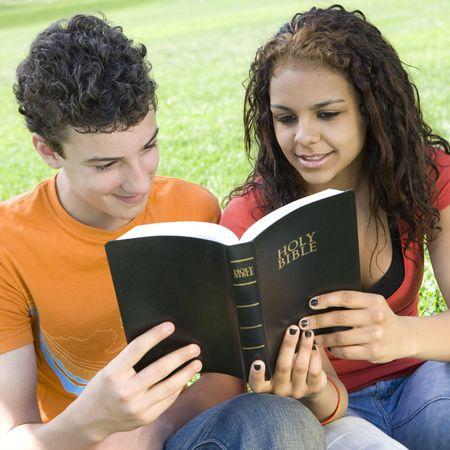 leyendo la biblia: Dos j�venes comparten una biblia en un parque Foto de archivo
