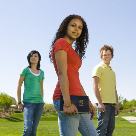 Three teenagers hang out in a park with a bible