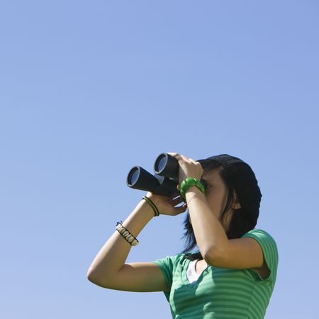 A teenager looks through binoculars