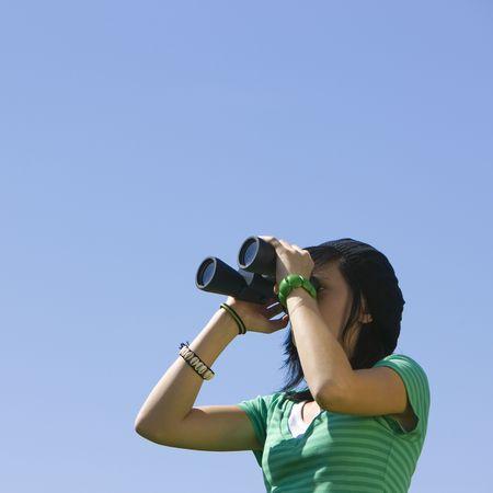 A teenager looks through binoculars