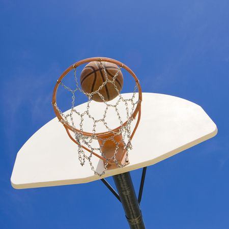 A basketball goes through a basketball hoop photo