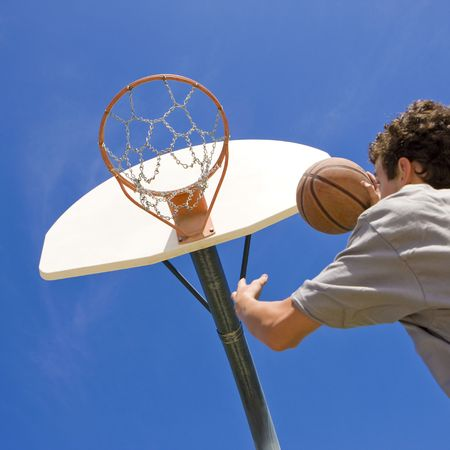 A teen basketball player jumps to shoot at the basket