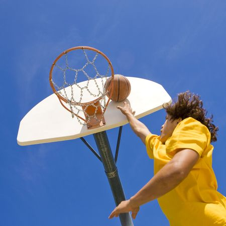 A teen basketball player jumps and shoots