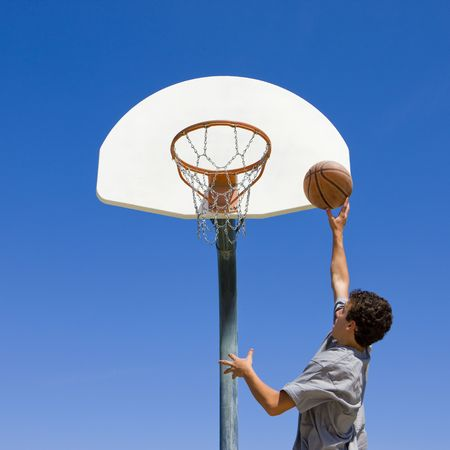 A teen boy jumps and shoots a basketbal Stock Photo